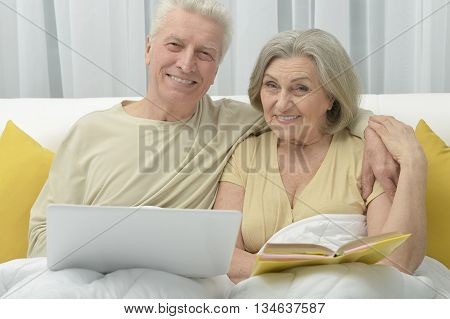 Senior couple resting and reading in bed
