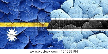 Nauru flag with Botswana flag on a grunge cracked wall