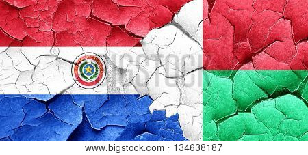 Paraguay flag with Madagascar flag on a grunge cracked wall