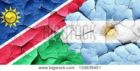 Namibia flag with Argentine flag on a grunge cracked wall