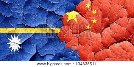 Nauru flag with China flag on a grunge cracked wall