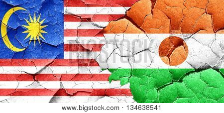 Malaysia flag with Niger flag on a grunge cracked wall
