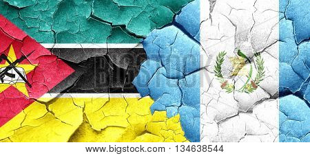 Mozambique flag with Guatemala flag on a grunge cracked wall
