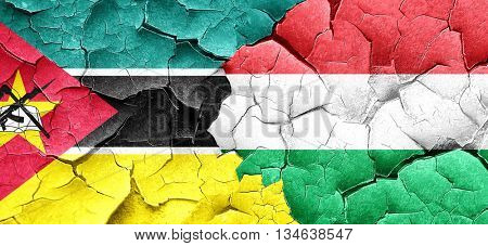 Mozambique flag with Hungary flag on a grunge cracked wall