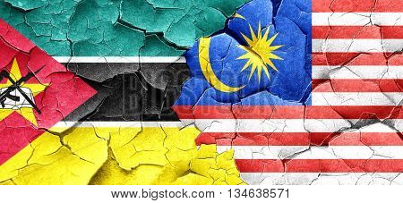 Mozambique flag with Malaysia flag on a grunge cracked wall