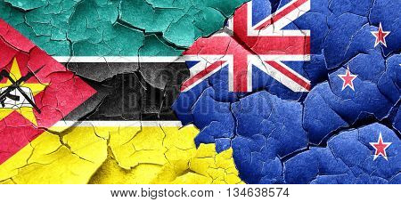 Mozambique flag with New Zealand flag on a grunge cracked wall