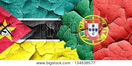 Mozambique flag with Portugal flag on a grunge cracked wall