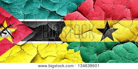 Mozambique flag with Ghana flag on a grunge cracked wall