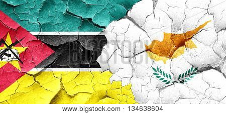 Mozambique flag with Cyprus flag on a grunge cracked wall