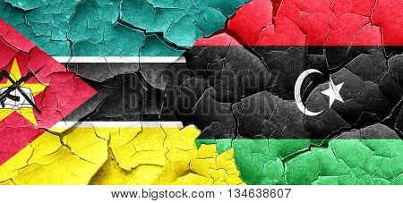 Mozambique flag with Libya flag on a grunge cracked wall