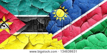 Mozambique flag with Namibia flag on a grunge cracked wall