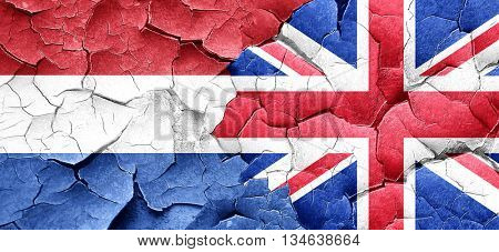 Netherlands flag with Great Britain flag on a grunge cracked wal