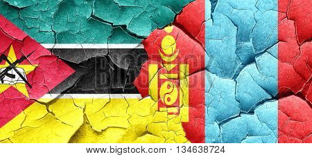 Mozambique flag with Mongolia flag on a grunge cracked wall