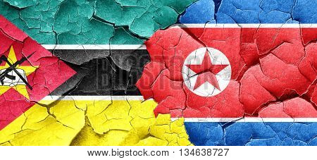 Mozambique flag with North Korea flag on a grunge cracked wall