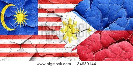 Malaysia flag with Philippines flag on a grunge cracked wall