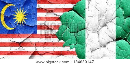 Malaysia flag with Nigeria flag on a grunge cracked wall