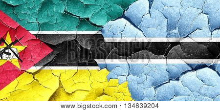 Mozambique flag with Botswana flag on a grunge cracked wall
