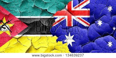 Mozambique flag with Australia flag on a grunge cracked wall