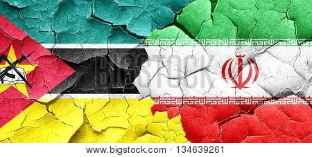 Mozambique flag with Iran flag on a grunge cracked wall