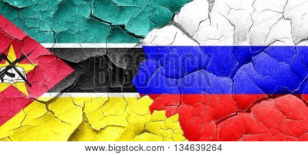 Mozambique flag with Russia flag on a grunge cracked wall