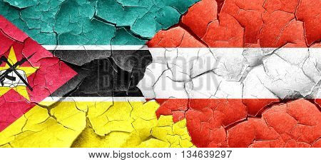 Mozambique flag with Austria flag on a grunge cracked wall