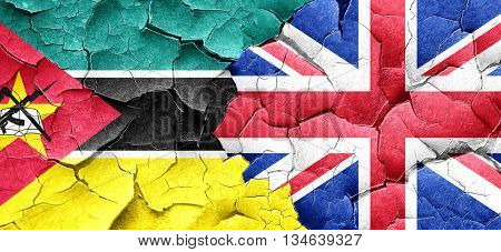Mozambique flag with Great Britain flag on a grunge cracked wall