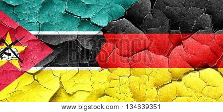 Mozambique flag with Germany flag on a grunge cracked wall