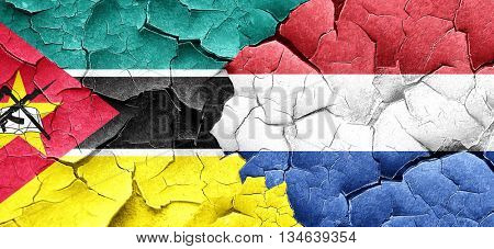 Mozambique flag with Netherlands flag on a grunge cracked wall