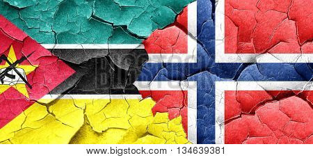 Mozambique flag with Norway flag on a grunge cracked wall