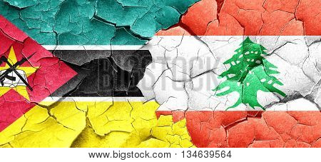 Mozambique flag with Lebanon flag on a grunge cracked wall