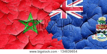 Morocco flag with Cayman islands flag on a grunge cracked wall