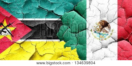 Mozambique flag with Mexico flag on a grunge cracked wall