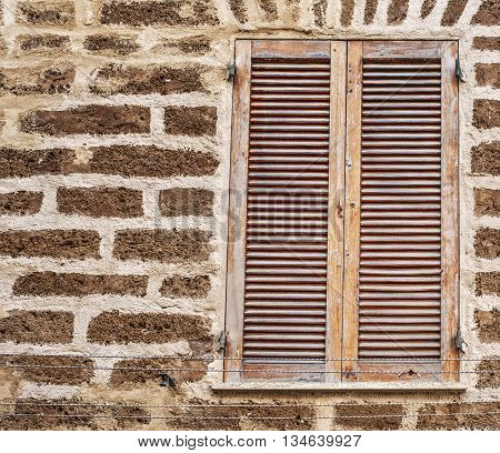 a closed window in a brick wall