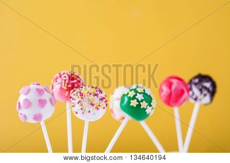 Sweet color cake pops on yellow background