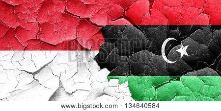 monaco flag with Libya flag on a grunge cracked wall