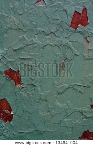 Vintage iron wall painted in green and blue with many layers of paint with cracks and rust