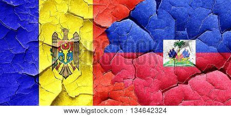 Moldova flag with Haiti flag on a grunge cracked wall