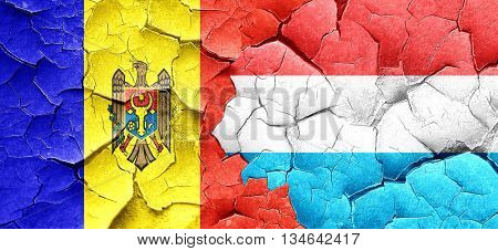 Moldova flag with Luxembourg flag on a grunge cracked wall