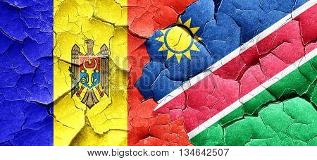 Moldova flag with Namibia flag on a grunge cracked wall