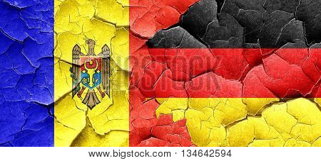 Moldova flag with Germany flag on a grunge cracked wall