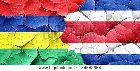 Mauritius flag with Costa Rica flag on a grunge cracked wall