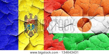 Moldova flag with Niger flag on a grunge cracked wall