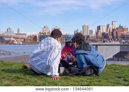 NEW YORK - MARCH 17, 2016: people take a rest at Pier 15 at daytime. Pier 15 is located east of South Street and FDR Drive in Lower Manhattan, New York City.