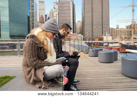 NEW YORK - MARCH 17, 2016: couple at Pier 15 at daytime. Pier 15 is located east of South Street and FDR Drive in Lower Manhattan, New York City.