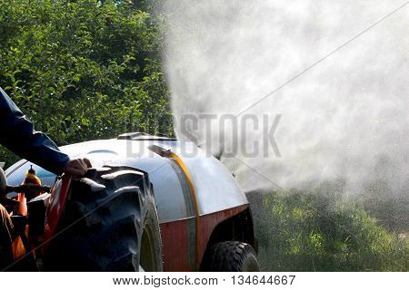 air blast sprayer with a chemical insecticide or fungicide in the orchard.pollution concept