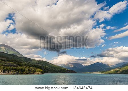 Blue Lake Amid Mountain Range And Dramatic Sky In Idyllic Uncontaminated Environment Once Covered By
