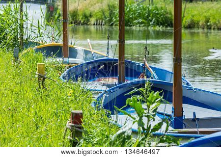 Schipluiden the Netherlands - June 16 2016: colourful sailing boats tied up to a river bank