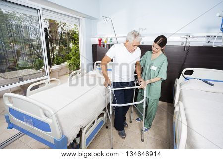 Nurse Helping Male Patient In Using Walker At Rehab Center