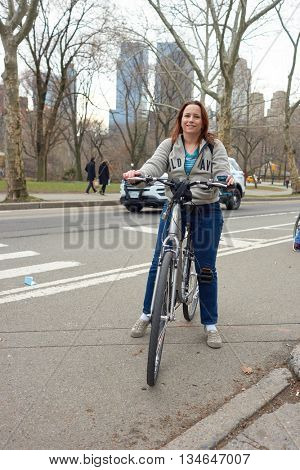 NEW YORK - CIRCA MARCH, 2016: outdoor portrait of woman with bicycle in Central Park. Central Park is an urban park in middle-upper Manhattan, within New York City.