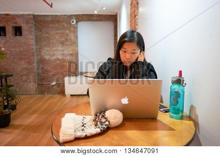 NEW YORK - CIRCA MARCH, 2016: woman with computer in the hostel. Hostels provide budget-oriented, sociable accommodation where guests can rent a bed
